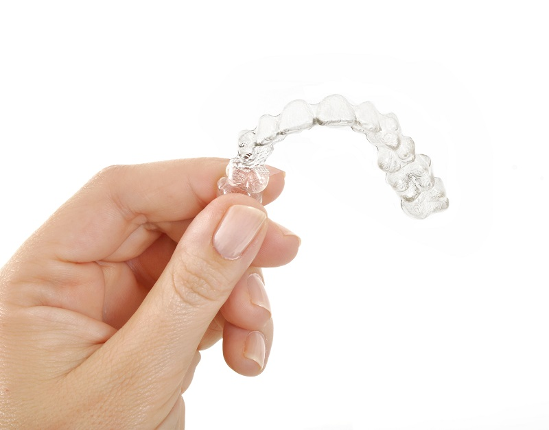 Person holding a set of ClearCorrect Invisible aligners