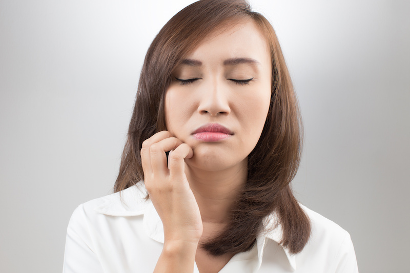 Woman suffering from TMJ disorder
