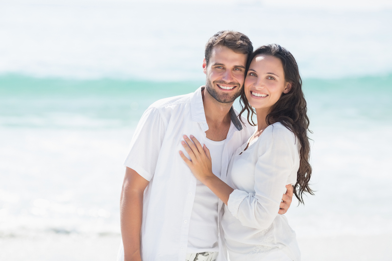 Attractive couple smiling on the beach after having smile makeovers