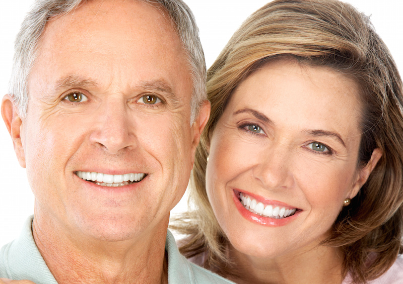 Elderly couple smiling, showing off nice teeth with porcelain veneers