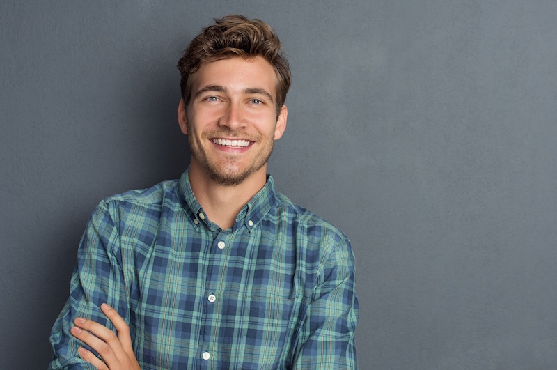 Young man in a plaid shirt shows off attractive smile after porcelain veneers